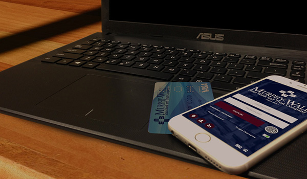 Photo of a laptop, murphy wall debit card and phone using the murphy wall app